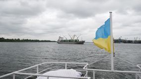 Ukrainian flag flies freely at back of boat on background of seaport with containers and cranes. Kherson, Ukraine 28 September 2017: Ukrainian flag flies freely stock video