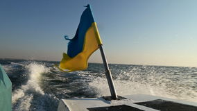 Ukrainian flag on a floating boat. Ukrainian flag on floating on the sea boat stock footage
