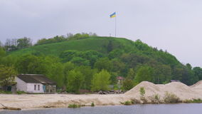 Ukrainian flag fluttering over Devich Mountain in Trypillia village stock video footage