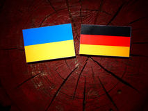 Ukrainian flag with German flag on a tree stump royalty free stock images