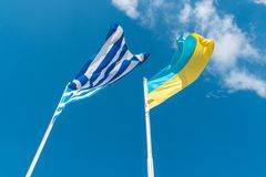 Ukrainian flag with Greek flag on background of sky stock images
