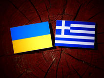 Ukrainian flag with Greek flag on a tree stump isolated Royalty Free Stock Photography