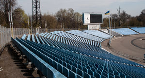 Ukrainian flag in the stadium. Seen at the stadium benches for spectators, the stands and the Ukrainian flag on a flagpole Stock Photos
