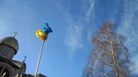 Ukrainian flag. Waving on cloudy pattern.  flying near the church and the tree stock footage