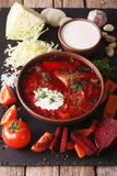 Ukrainian food: red soup borsch with ingredients on slate board. Closeup. vertical Royalty Free Stock Photography