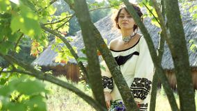 Ukrainian girl with a bouquet posing on camera between branches of red viburnum. Ukrainian girl posing on camera between branches of red viburnum. Slow motion stock video