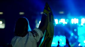 Ukrainian girl in Embroidery waving the national flag at a rock concert, on a background of a large number of concert. Spectators, bright colored lights of the stock video footage