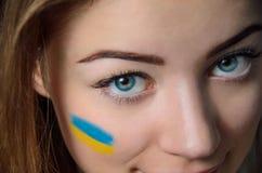 Ukrainian girl. Girl with Ukrainian flag on her cheek Stock Photo