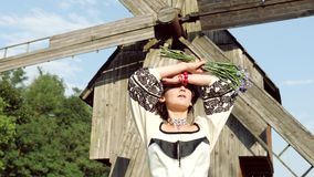 The ukrainian girl lifts hands up to her head enjoying leisure in the village. The ukrainian girl in sun rays walking near old Ukrainian mill and then lifts stock video footage