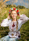Ukrainian girl in national clothes sitting on meadow Stock Image