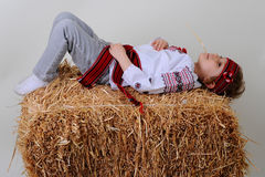Ukrainian girl in national dress and blue jeans lies on a haysta. Ck Royalty Free Stock Photography