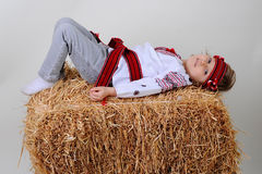 Ukrainian girl in national dress and blue jeans. Lying on a haystack and laughs Royalty Free Stock Photo