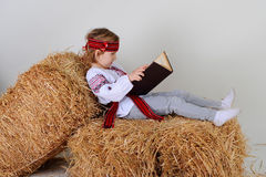 Ukrainian girl in national dress with a book. Ukrainian girl in national dress and blue jeans lying on a haystack and reading Royalty Free Stock Photos