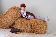 Ukrainian girl in national dress with a book Capital. Ukrainian girl in national dress and jeans with the book Capital lies on a haystack Royalty Free Stock Images