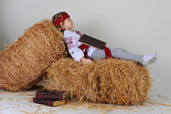 Ukrainian girl in national dress with a book Capital. Ukrainian girl in national dress and jeans with the book Capital lies on a haystack and sleeps Royalty Free Stock Photo