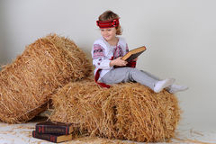 Ukrainian girl in national dress with a business book. Ukrainian girl in national dress and jeans with economic book in Russian lying on a haystack Royalty Free Stock Images
