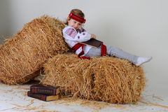 Ukrainian girl in national dress with a business book. Ukrainian girl in national dress and jeans with a business book lying on a haystack Royalty Free Stock Photos
