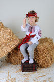 Ukrainian girl in national dress with economic book. Ukrainian girl in national dress and jeans sitting on a haystack legs on economic books Royalty Free Stock Photography