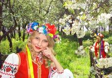 Ukrainian girl in national dress in a flowering garden. Ukrainian girl in national dress in a flowering spring garden Royalty Free Stock Photos
