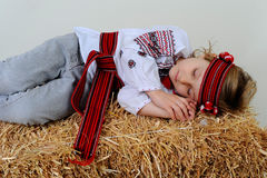Ukrainian girl in national dress and jeans sleeping in the hay. Ukrainian girl in national dress and jeans sleeps on a haystack Royalty Free Stock Photography