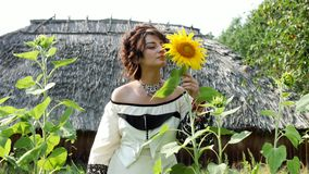 Ukrainian girl sniffs sunflower, enjoys nature and then leaves. In the background, the Ukrainian hut with thatched roof. Romantic, sensual, enigmatic, playful stock footage