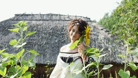 Ukrainian girl sniffs sunflower, enjoys nature and then leaves. In the background, the Ukrainian hut with thatched roof. Romantic, sensual, enigmatic, playful stock video footage