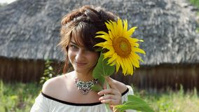 Ukrainian girl sniffs and touches sunflower, enjoys nature and then leaves. Ukrainian girl sniffs and touches sunflower, enjoys nature. In the background, the stock video footage