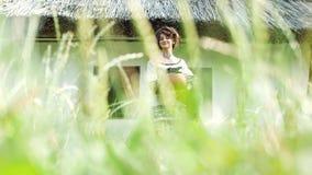 A Ukrainian girl is standing near the hut in the grass. A Ukrainian girl is standing near a Ukrainian hut in the grass with a bouquet and a jug in her hands stock video