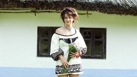 A Ukrainian girl stands near a Ukrainian hut. A Ukrainian girl stands near a Ukrainian hut with a bouquet of statice in her hands and smiles at the camera. On stock footage