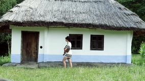 A Ukrainian girl is wolking near the hut with a jug. Slow motion stock video footage