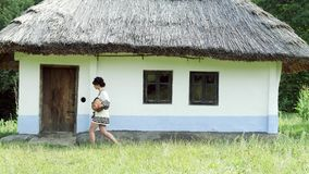 A Ukrainian girl is wolking near the hut with a jug. Slow motion stock footage