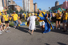 Ukrainian grandma dance with swedish football fans. Fans of the Swedish national football team have fun during Euro-2012 in Kiev, Ukraine Royalty Free Stock Photography