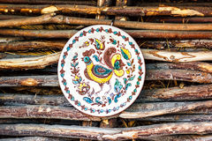 Ukrainian handmade earthenware utensil. Painted plate on wooden wall. Souvenirs From Ukraine in ethnic style. Stock Image