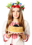 Ukrainian holds pancakes. Ukrainian woman in a wreath holds pancakes with caviar royalty free stock image