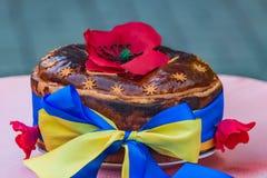 Ukrainian homemade festive bread. Ukrainian, homemade festive bread, decorated with red poppies and yellow-blue ribbon which symbolizes the Ukrainian flag Stock Photo
