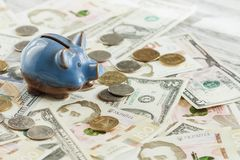 Ukrainian hryvnia, American dollars and a piggy bank. Soft focus background Stock Image