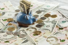 Ukrainian hryvnia, American dollars and a piggy bank. Soft focus background Stock Photography