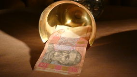 Ukrainian hryvnia dropped out of the golden cup stock footage