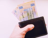 Ukrainian hryvnia money lies in the parcel. Ukrainian money and passport are on the table in a brown purse stock image