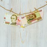 Ukrainian hryvnia and Russian rubles suspended on clothespins. Money laundering, currency fraud and corruption concept. Ukrainian hryvnia and Russian rubles royalty free stock photography