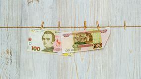 Ukrainian hryvnia and Russian rubles suspended on clothespins. Money laundering, currency fraud and corruption concept. Ukrainian hryvnia and Russian rubles stock photo