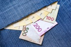 Ukrainian hryvnia sticking out of a torn blue denim pocket. Sharing a business concept. Ukrainian hryvnia falls out of a torn denim pocket. 100, 200 and 500 stock photos