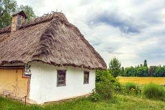 Ukrainian hut thatched sloping field near Royalty Free Stock Photography