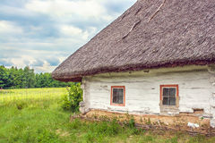 Ukrainian hut thatched sloping field near Stock Photo