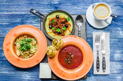 Ukrainian lunch: frying pan with potatoes and meat, red soup, salad of vegetables and herbs, bread, coffee and cutlery, on a blue Royalty Free Stock Image