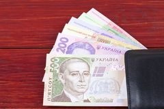 Ukrainian money in the black wallet. On a wooden background stock photo