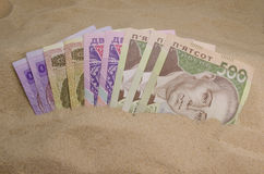 Ukrainian money in sand Stock Photos