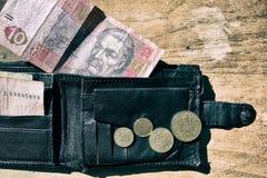 Ukrainian money in the wallet on black background. Ukrainian money in your wallet little my coins Stock Photos