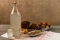Ukrainian national drink and snack. The big bottle and glass of moonshine on the old wooden table. Russian vodka and snack. Royalty Free Stock Photography