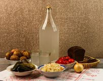Ukrainian national drink and snack. The big bottle and glass of moonshine on the old wooden table. Russian vodka and snack. Royalty Free Stock Photos